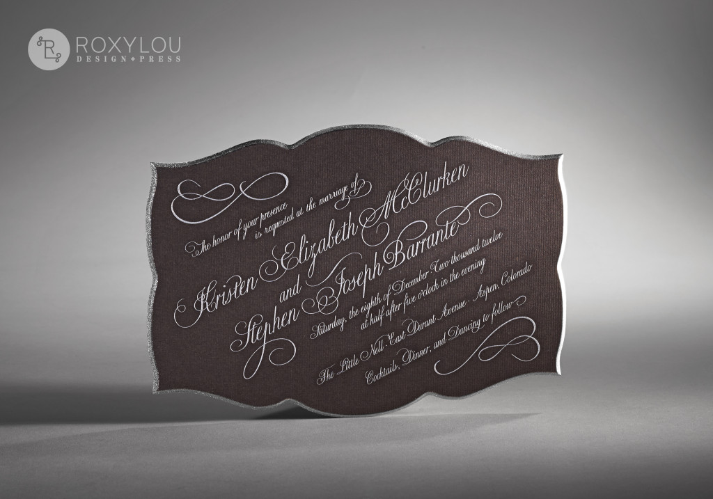The Flourish wedding invitation suite makes a stunning statement in your guests' mailboxes. This very thick invitation features engraved printing and a beveled, painted edge. Text set on an angle is modern and beautiful. The inner envelope also features edge painting on the flap. Beautiful as pictured in brown and silver, but let us create this in your color scheme for a truly unique wedding invitation.