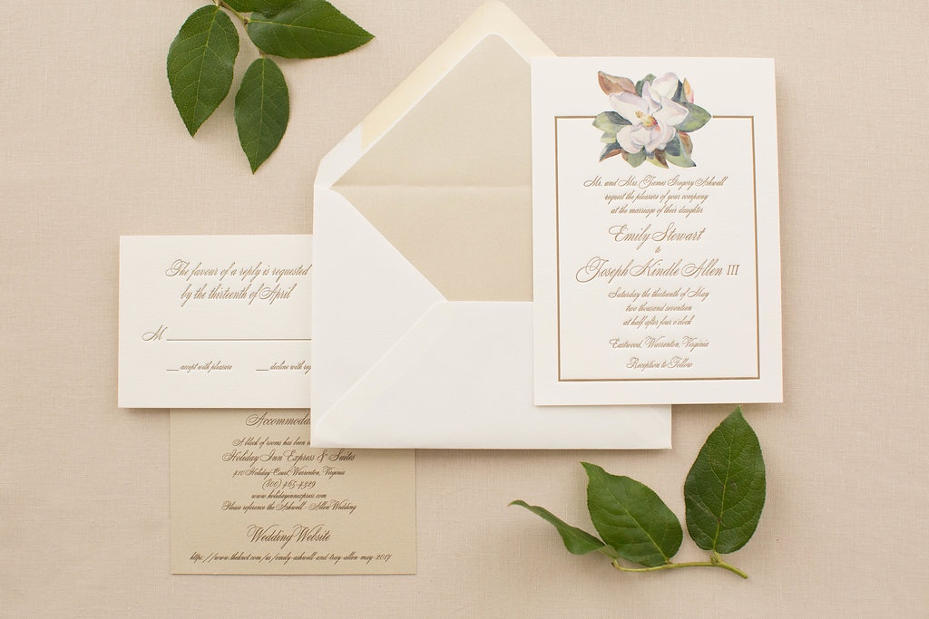 Watercolor magnolia graces the top of this beautiful letterpress wedding invitation with script and a delicate border.  All accented with champagne papers