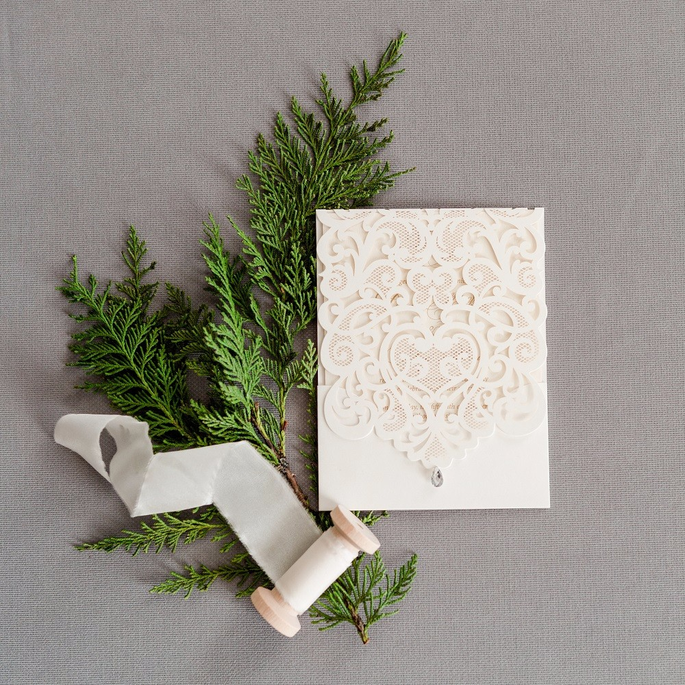 A shimmery ivory lasercut folder encloses a traditional gold toned thermographed wedding invitation and response set.