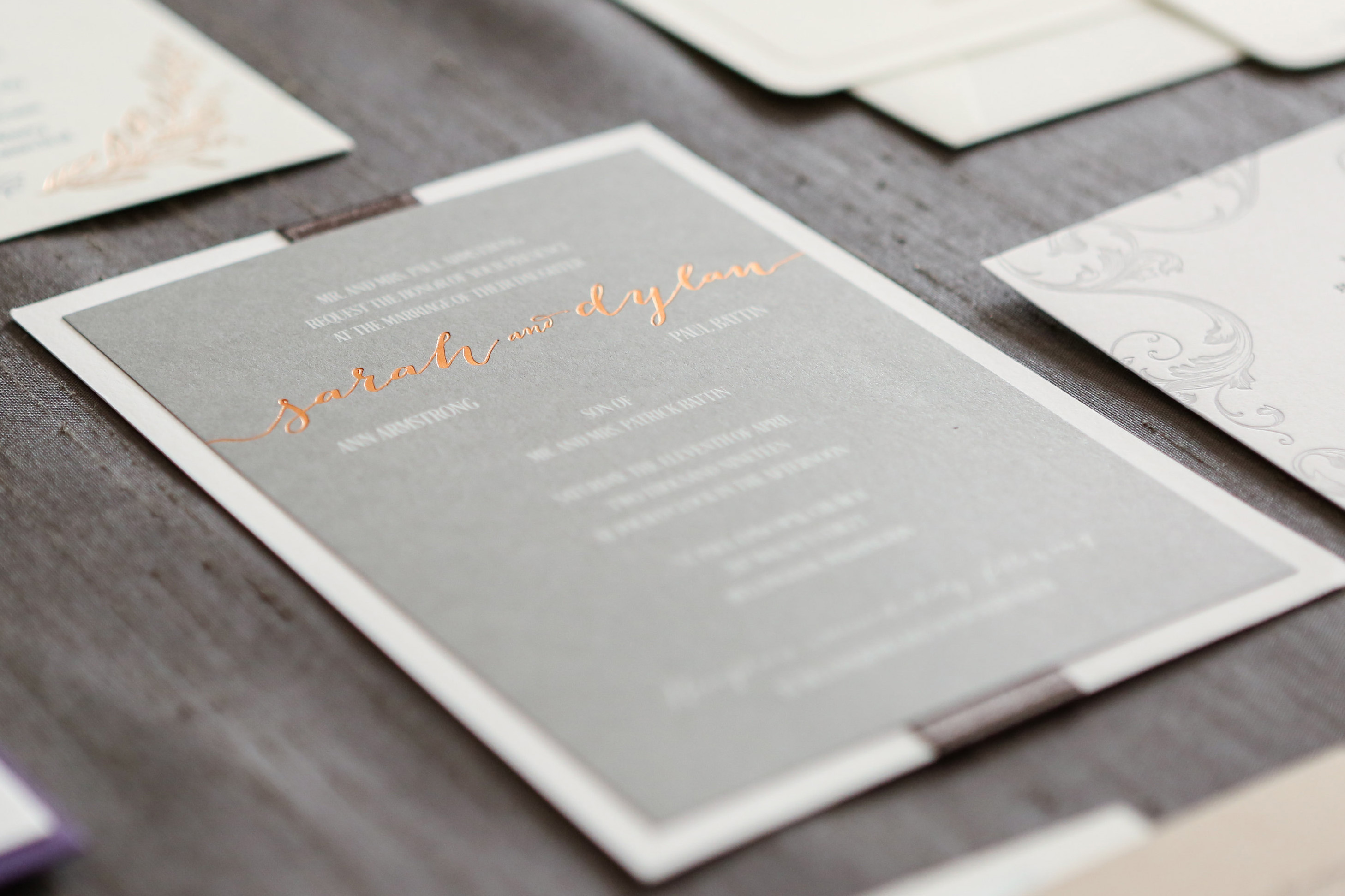 Copper foil is a stunning accent on this charcoal gray wedding invitation featuring a white backing layer and gray satin ribbon accent.