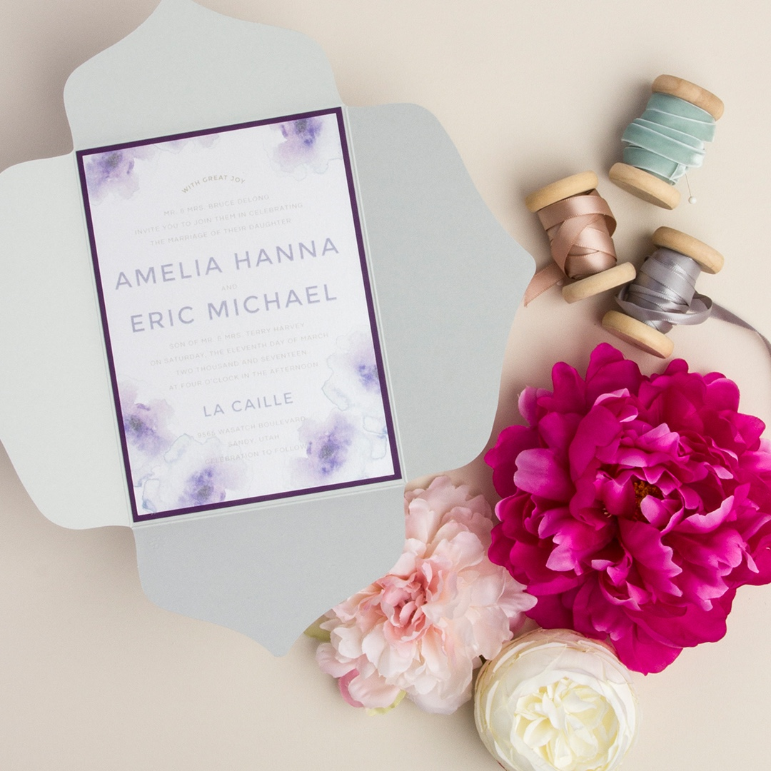 Water lilies pointed petal fold wedding invitation by Envelopments features watercolor art embellishing the corners.