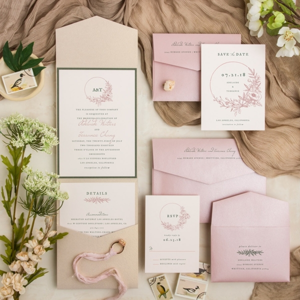 Enchanted Wreath layered pocketfold wedding invitation in beige, green, and pink.