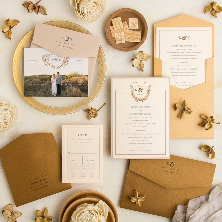 Open Highway framed wedding invitation with monogram crest in gold.