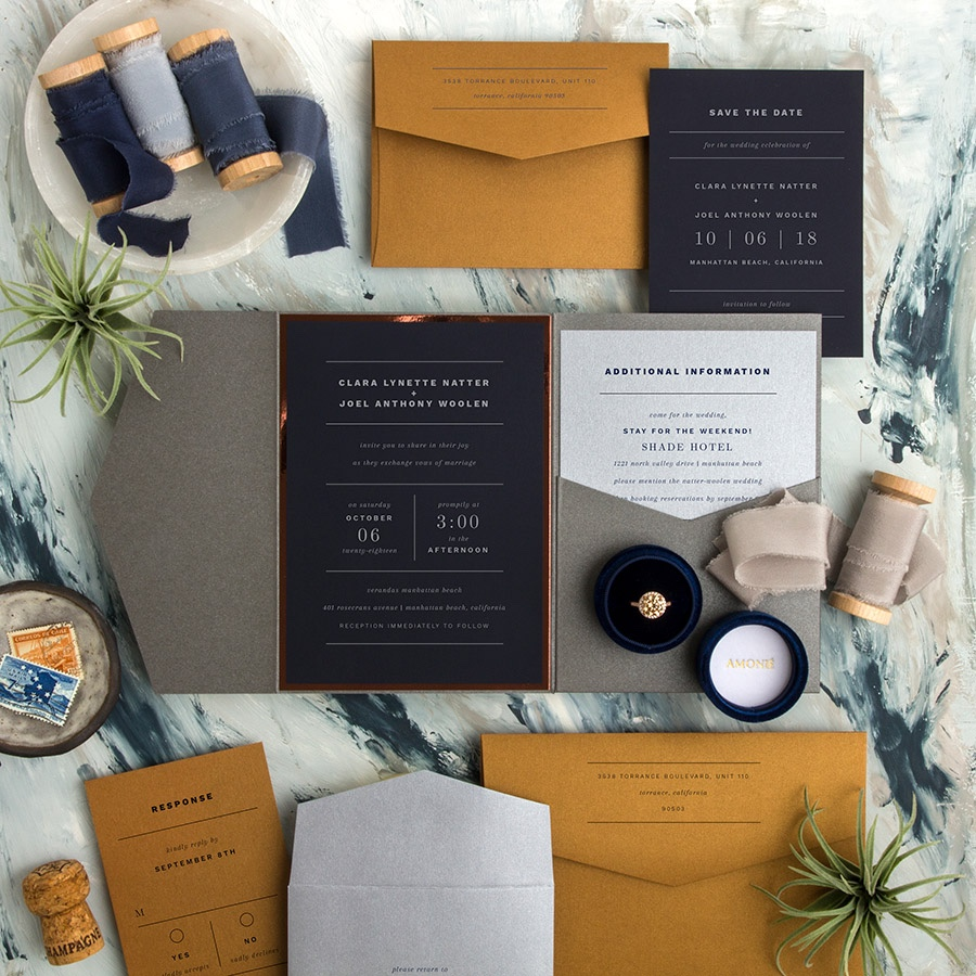 Young Love striking contemporary wedding invitation white ink on navy with copper accent and gray pocket folder.