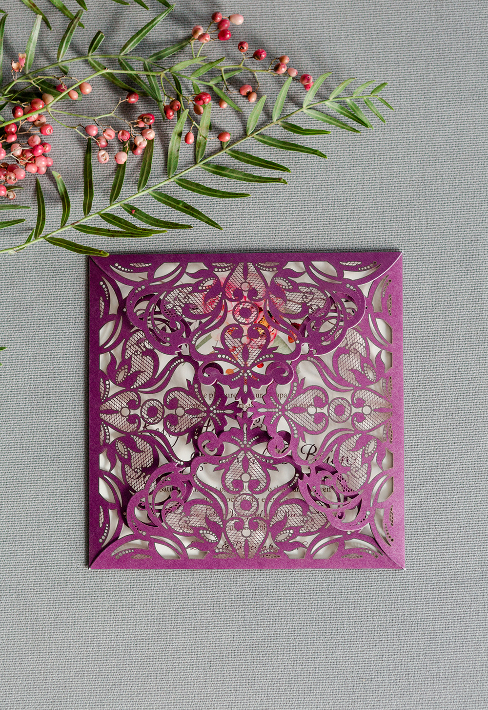 Shimmery purple lasercut folio encloses a fall floral embellished wedding invitation.