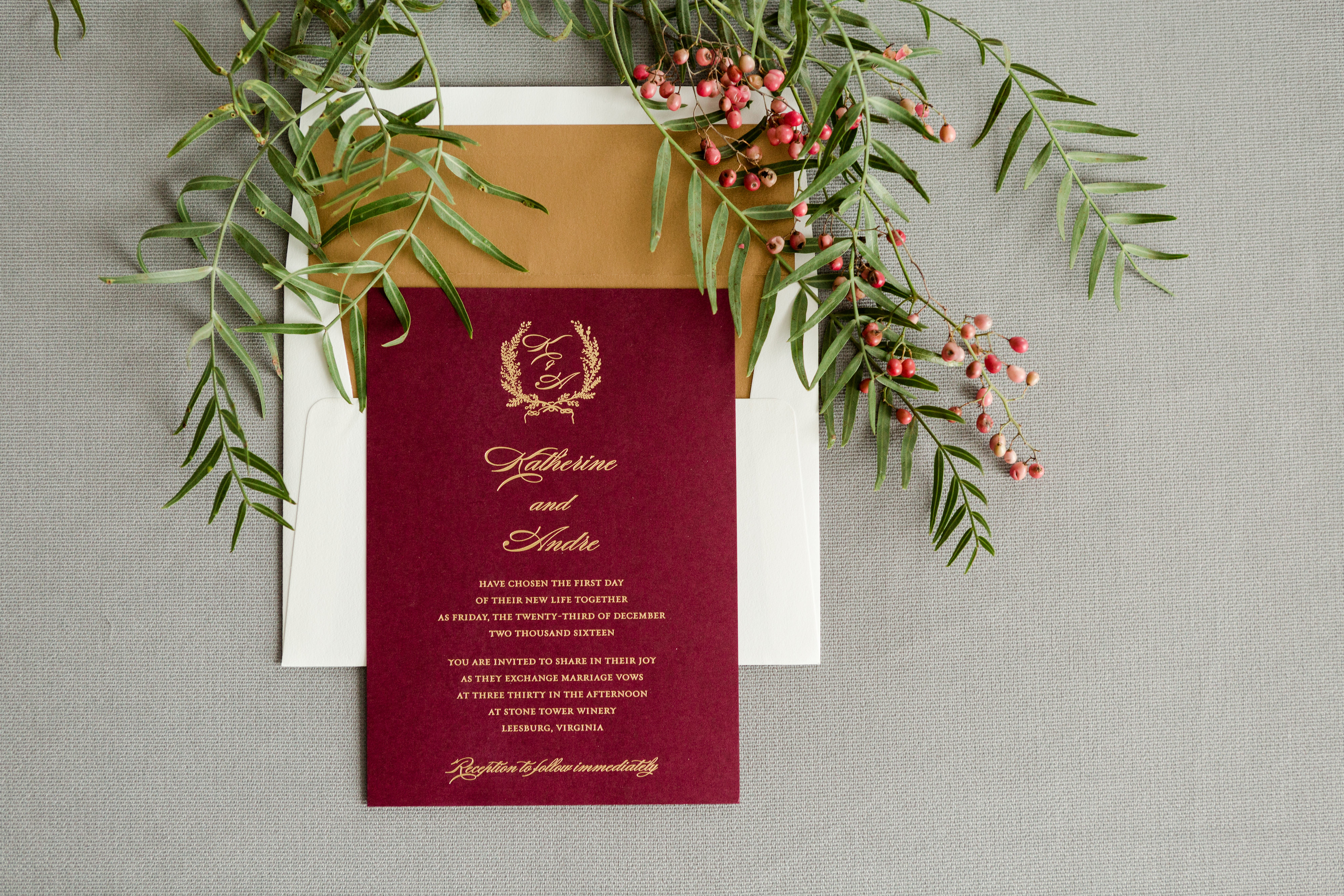 Wine colored invitation with gold foil stamping featuring a laurel monogram