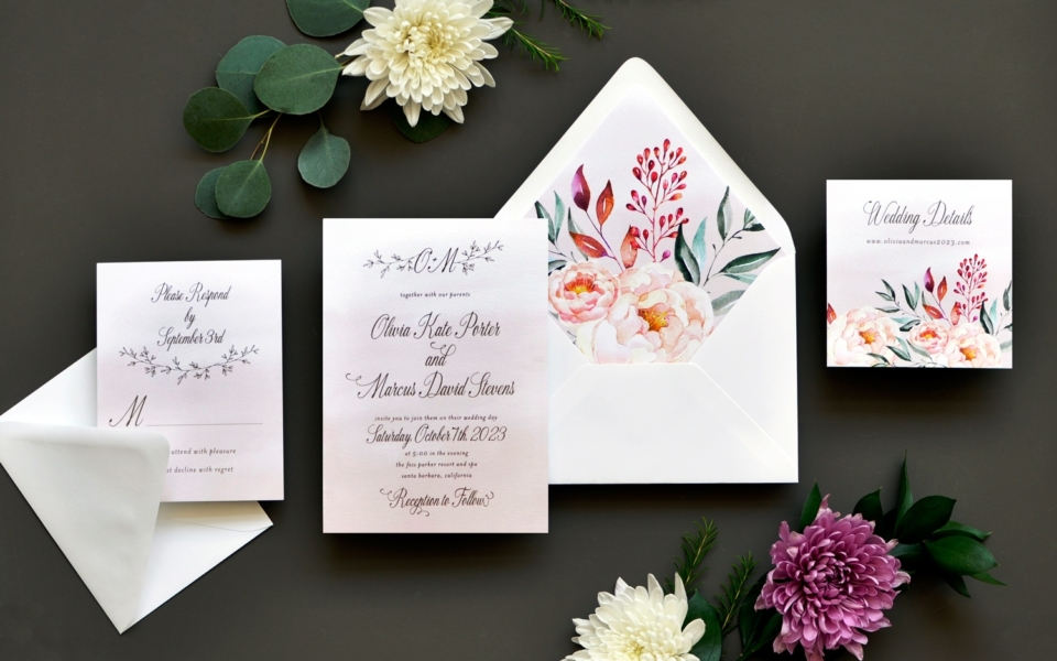 A colorful bouquet of flowers in the envelope liner and on the details card is a beautiful pairing to a blush watercolor wash background of the contemporary invitation featuring a monogram at the top.