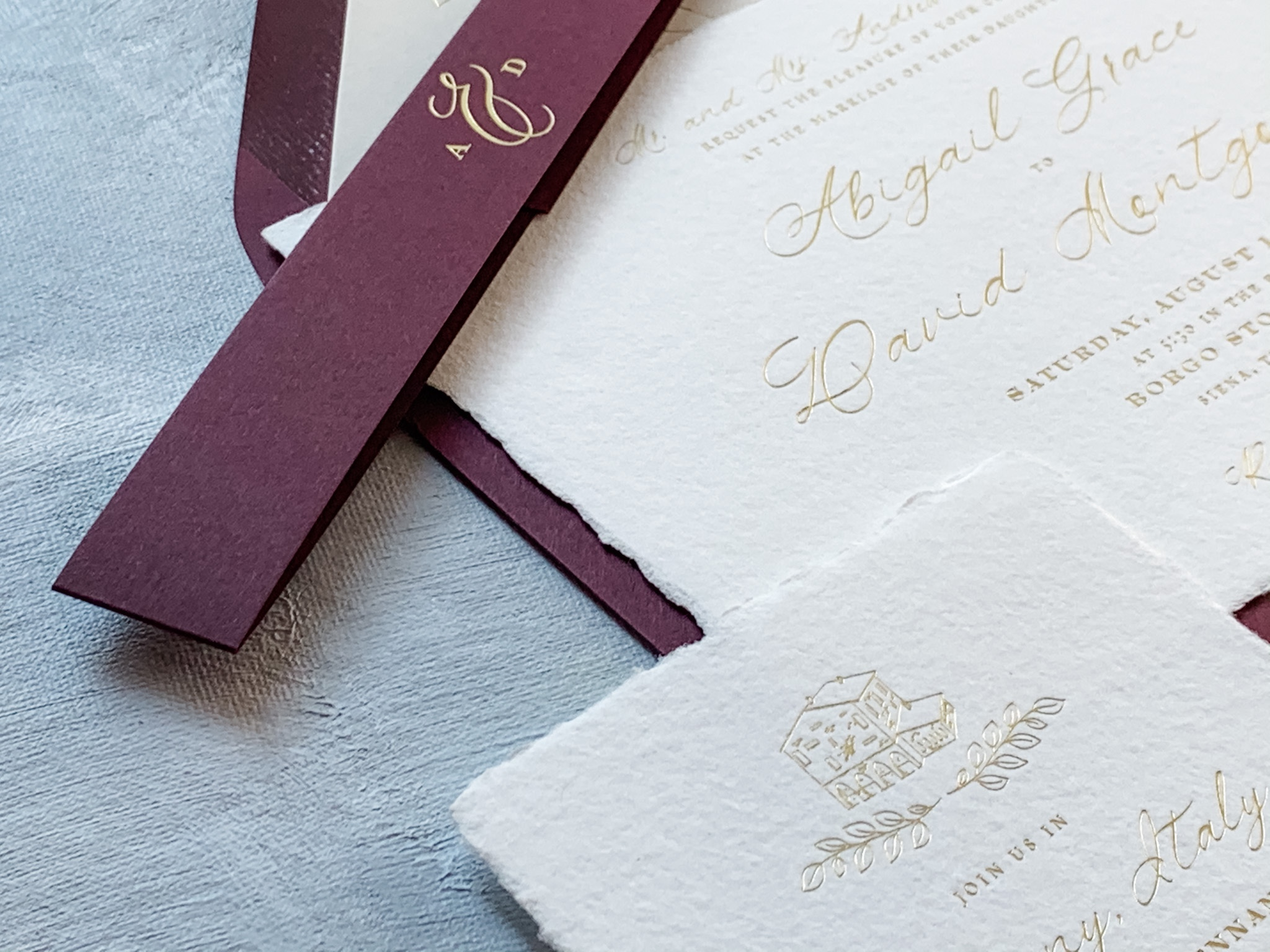 Handmade paper with a deckled edge is expertly foil stamped and accented with a wine colored belly band and  envelope.