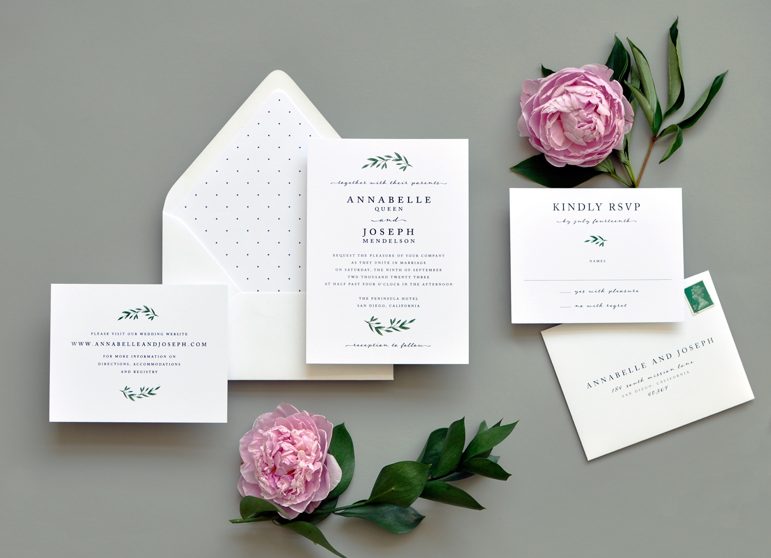 Contemporary text setting is embellished with a spray of greenery and accented with delicate script. A subtle polka dot envelope liner is the perfect pairing.