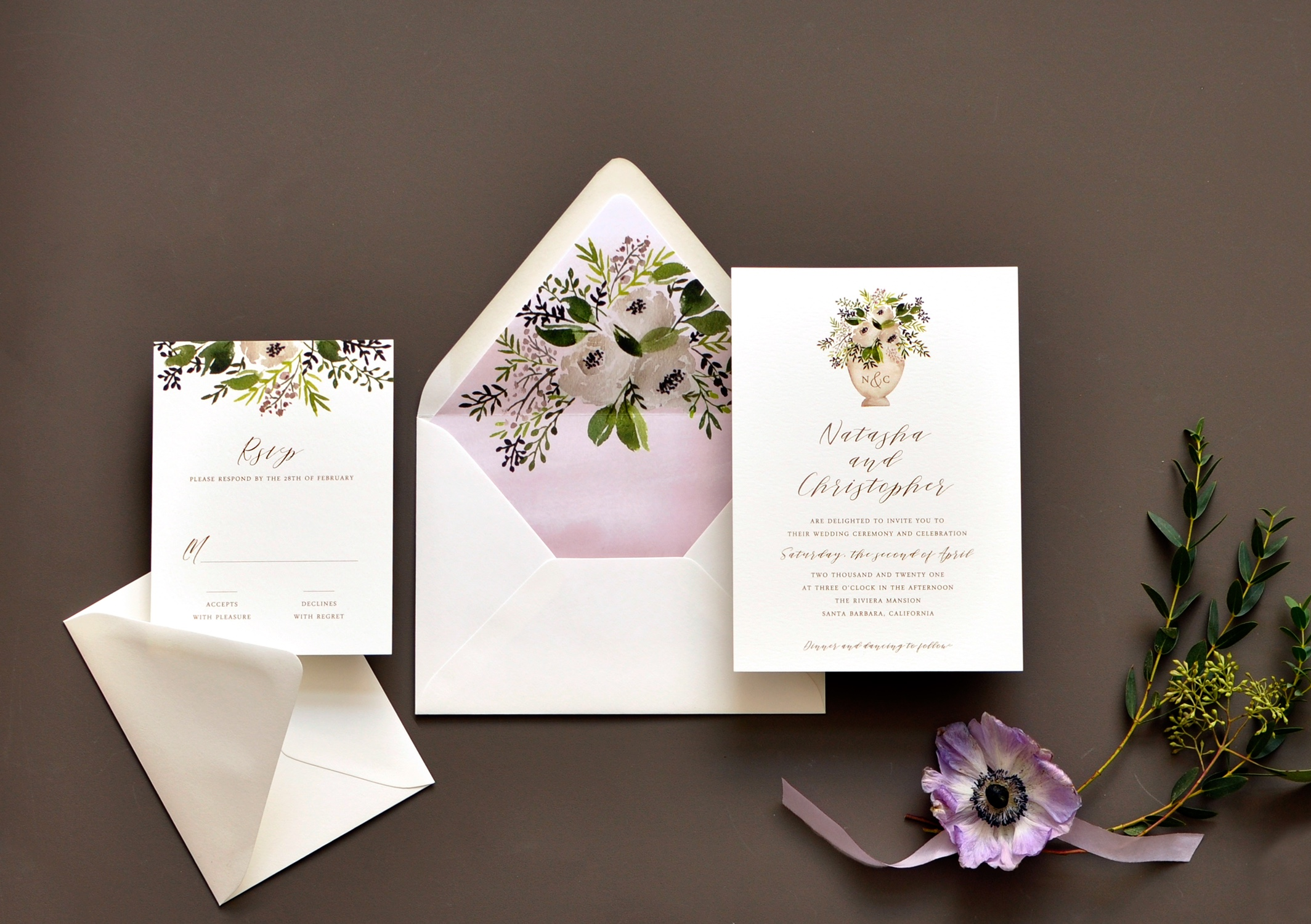 A planter of neutral flowers and pretty greenery graces the top of this contemporary calligraphy invitation perfect for a garden wedding.