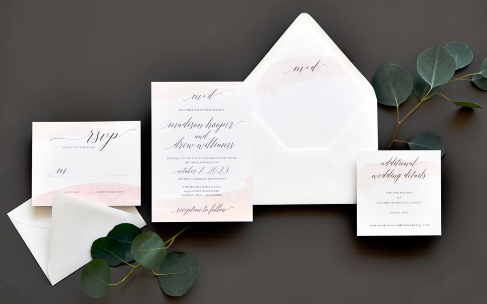Pale blush brushstrokes are an elegant accent to pretty calligraphy text on this modern wedding invitation.