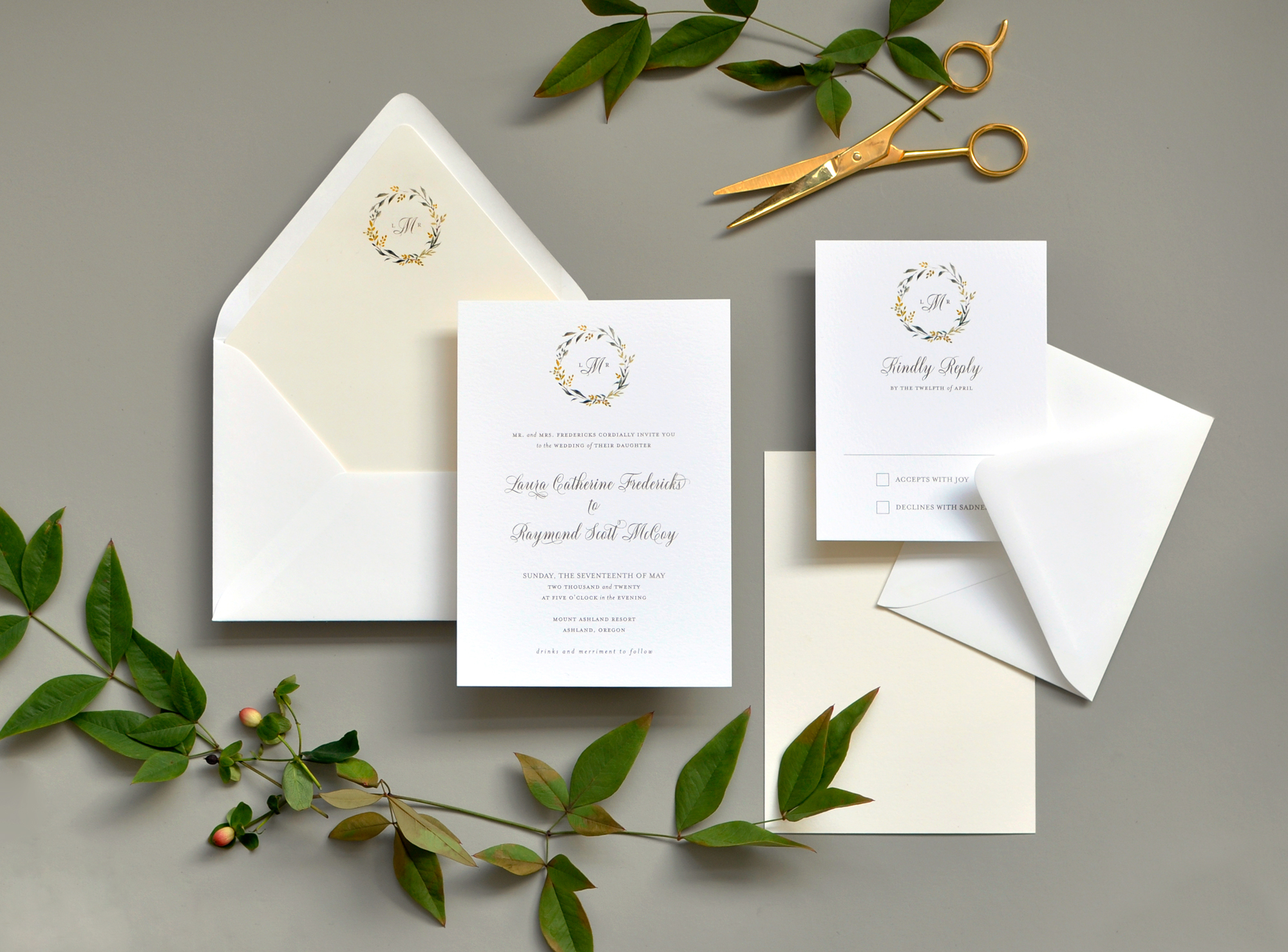 A pale yellow and greenery floral wreath circles a monogram at the top of this simple, yet sweet botanical wedding invitation.