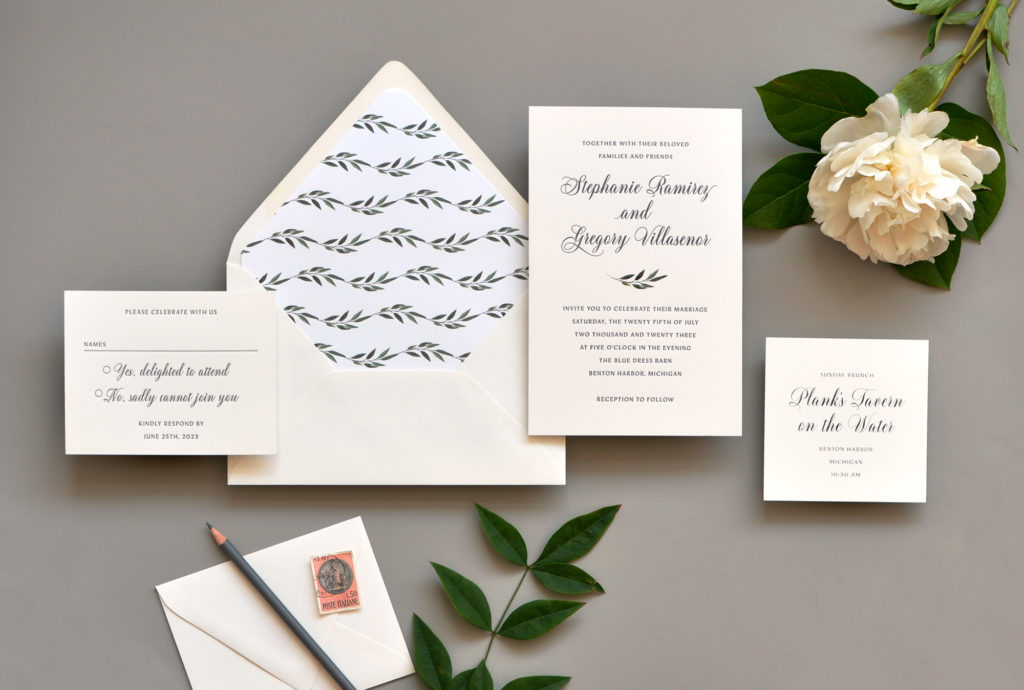 contemporary wedding invitation is embellished with a subtle leaf branch.