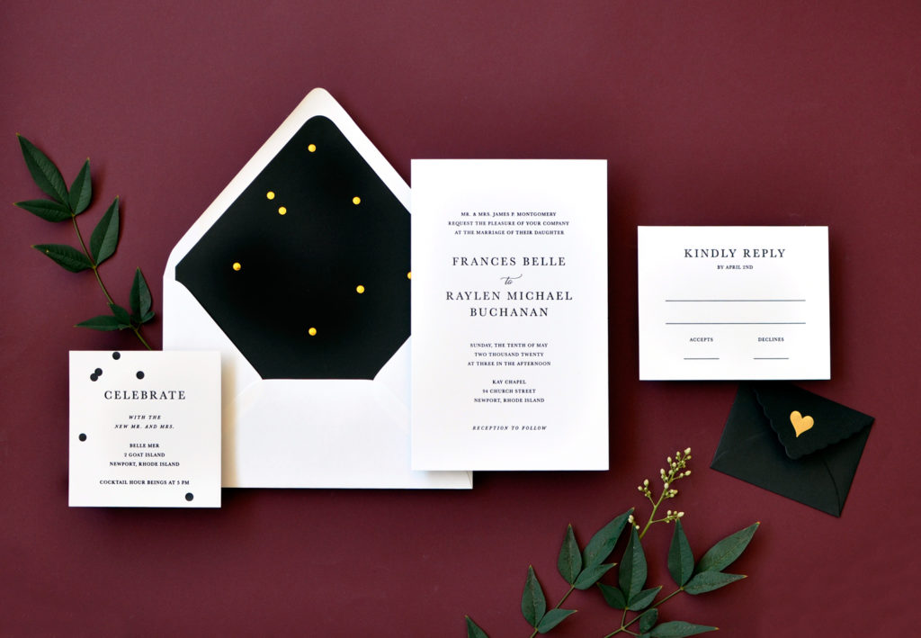 Stunning contemporary wedding invitation in black letterpress is embellished by a dramatic black envelope liner touched gracefully with confetti of gold foil.