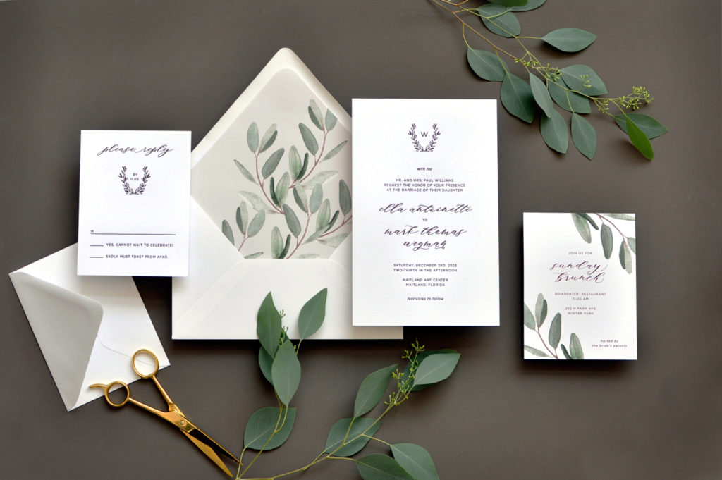 A wreathed monogram adorns the top of this contemporary letterpress wedding invitation with modern calligraphy available at Staccato.