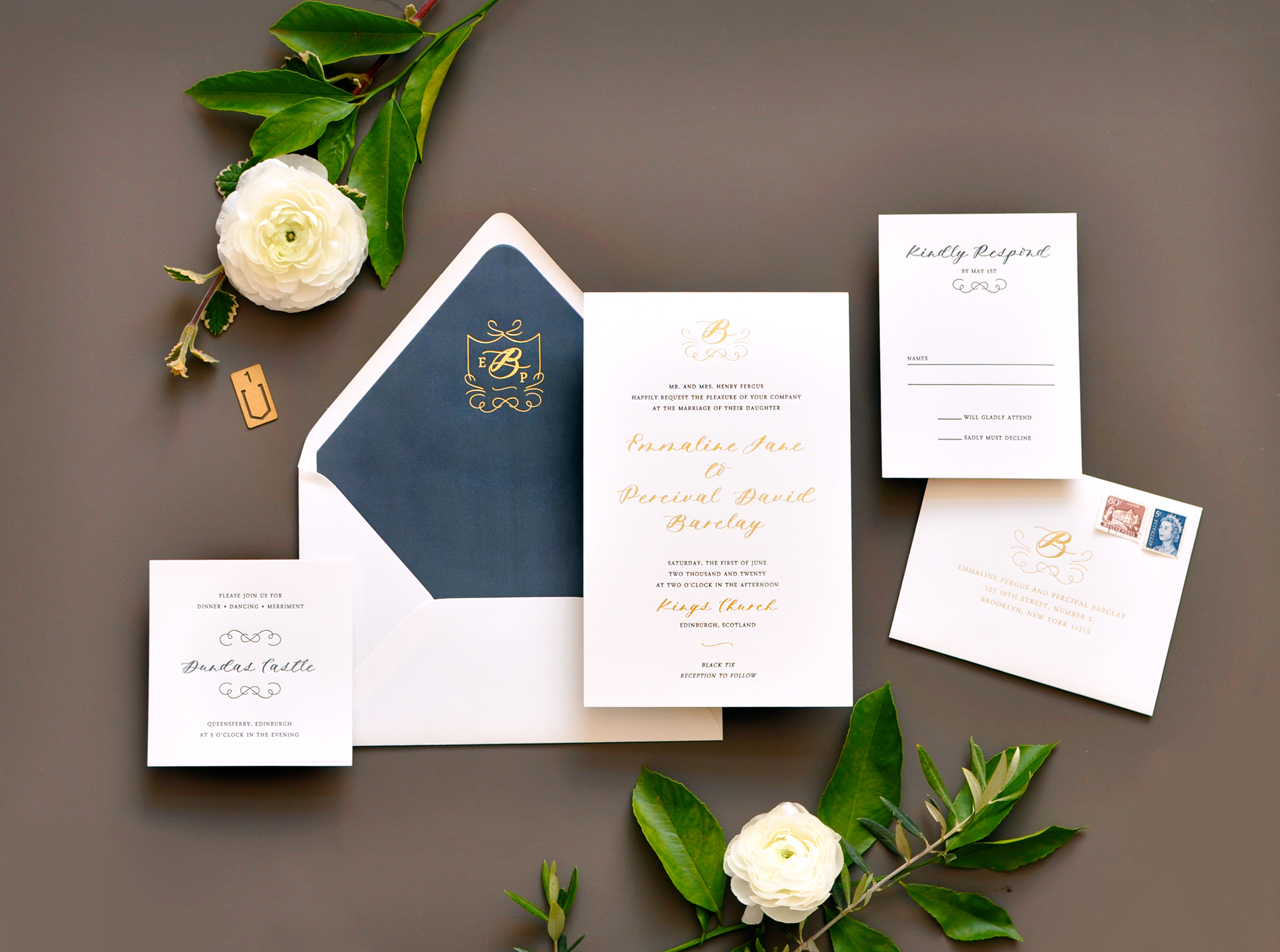Gold foil and navy letterpress are the perfect pairing on this formal wedding invitation embellished with a flourished monogram and personalized envelope liner.