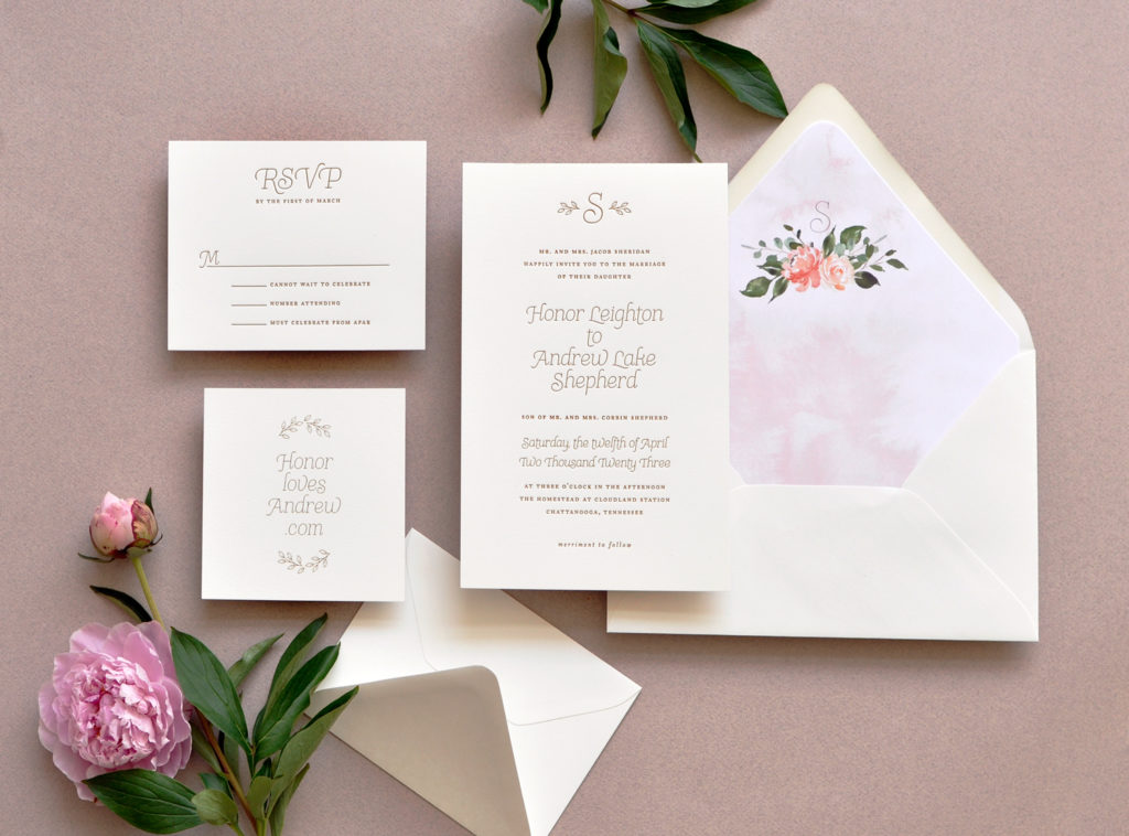 A delicate monogram graces the top of this contemporary wedding invitation that features a floral bouquet on a watercolor envelope liner.