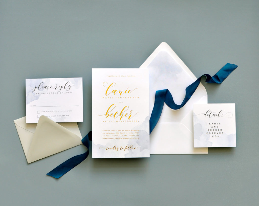 Bold gold foil printing on a delicate watercolor washed background is a stunning wedding invitation offered by Staccato in Fairfax, Virginia.