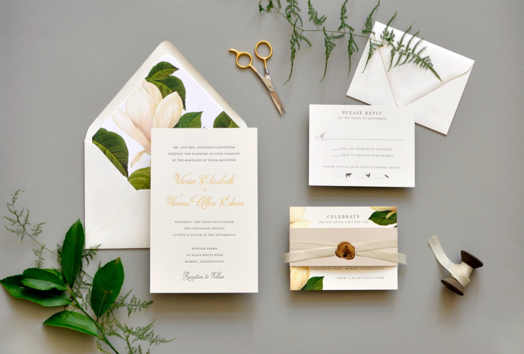 Classic letterpress and gold foil wedding invitation features a large white magnolia on the lined envelope and as embellishment on the information insert.
