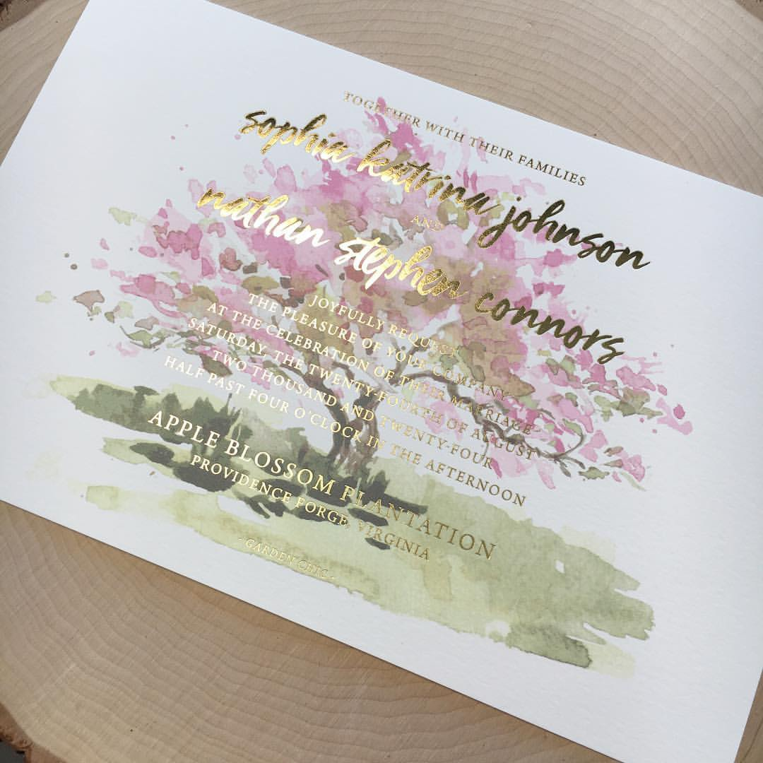 Beautiful watercolor tree in bloom is set behind pretty gold foil text.