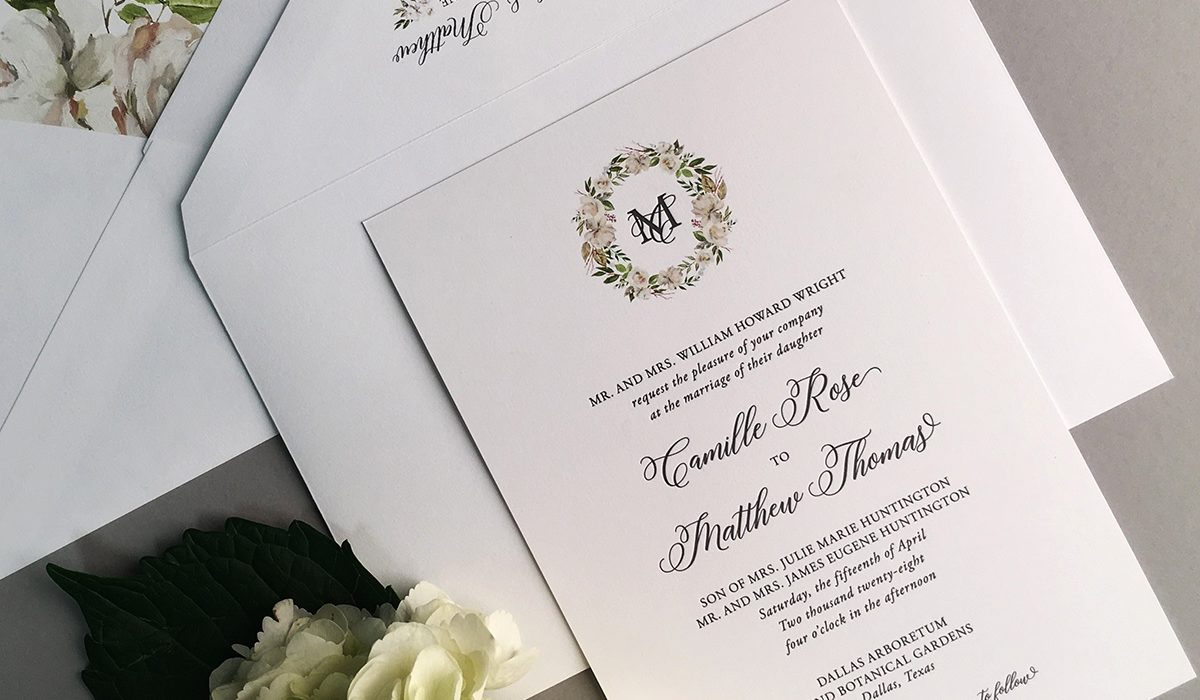 Luxury letterpress wedding invitation features traditional layout with calligraphy accents and a beautiful watercolor floral wreath around the monogram.
