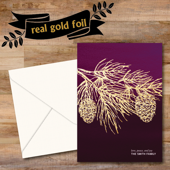Golden tree branch with pine cone is hot foil stamped onto a watercolor wine background with personalized text printed in lower right hand corner.