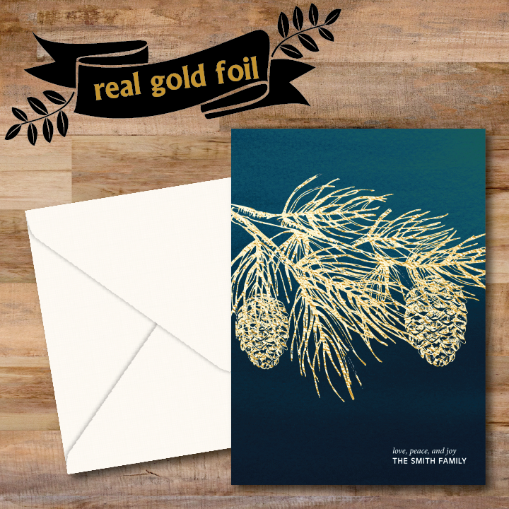 Branch of evergreen tree with pine cones is hot foil stamped into a teal watercolor background.  Personalized holiday greeting is printed in the lower right hand corner.