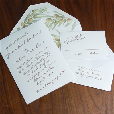 Angled script on a deckled edge paper makes one feel as though they're receiving a highly personal, hand-written invitation!  Accented with olive branches in the envelope liner, this wedding invitation in letterpress is truly a trip to the Old World!