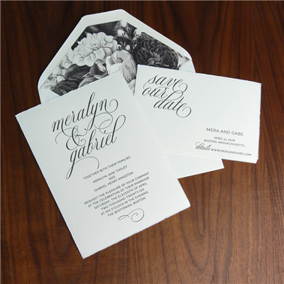 This contemporary wedding invitation suite features bold names in a large script across the top and a black and white floral envelope liner.