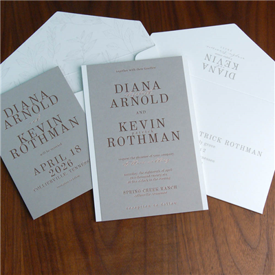 copper foil stamping on gray paper with white horizontal borders.  Names are set in a bold, strong typestyle in this contemporary wedding invitation.