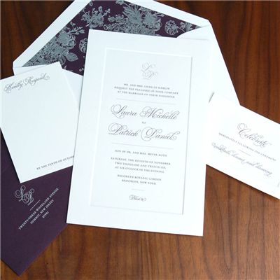 An embossed frame surrounds this traditional wedding invitation with a modern script, delicate monogram, and contemporary dividing lines.  Deep eggplant envelope liner is foil stamped.