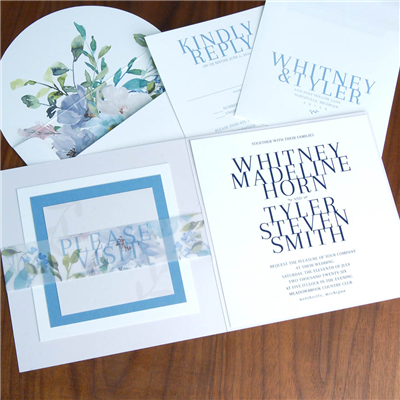 A truly unique wedding invitation features a book style fold, floral printed vellum band for holding inserts, and bold text setting.
