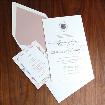 A beautiful floral crest sets the monogram at the top of this flourished, traditional wedding invitation.  Floral accents, vertical envelope, gold foil stamping.