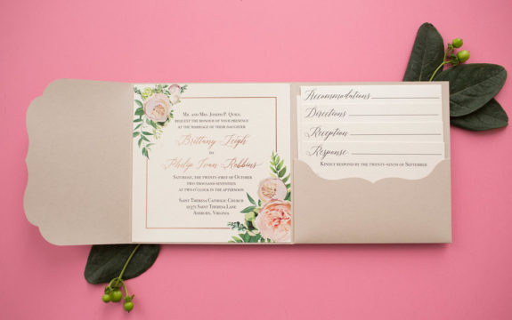 Rose gold foil stamped wedding invitation with floral motif in a scalloped pocketfolder.