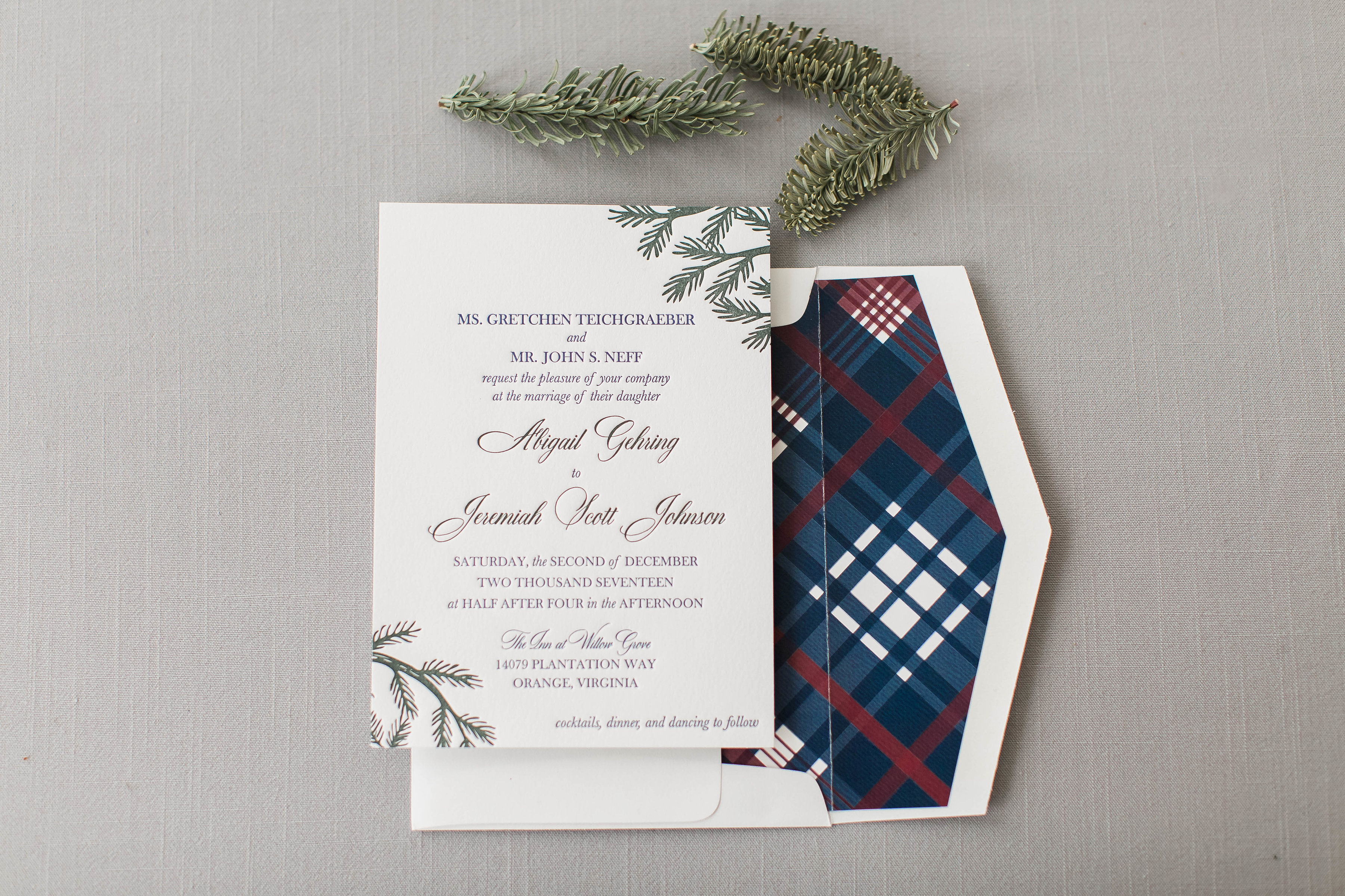 Custom letterpress wedding invitations feature olive evergreen branches and a blue and red plaid envelope liner.