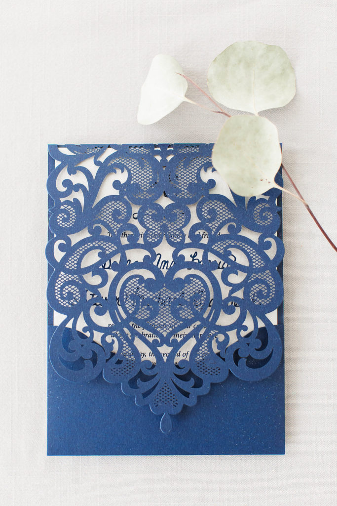 navy lasercut invitation folio houses a silver invitation with navy thermography printing and custom lettering