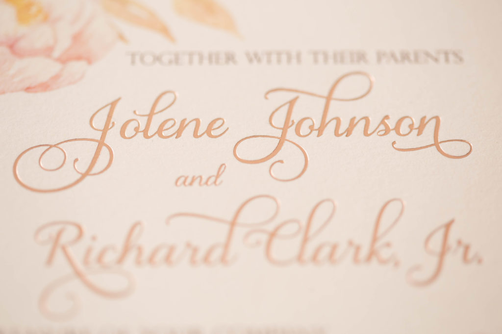 a metallic ivory lasercut folio with 4 folding points encloses a beautiful watercolor floral wedding invitation that is accented with rose gold foil.