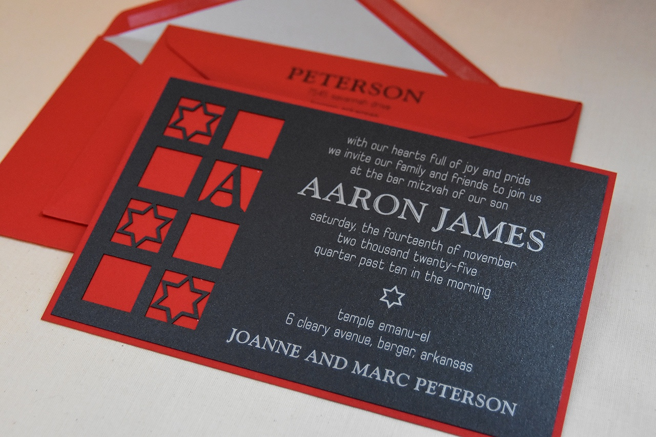 Aaron James dramatic lasercut black bar mitzvah invitation is layered onto red and features white text.  Available for DC, MD, and VA celebrations at Staccato.