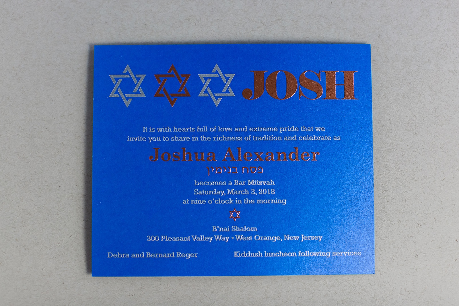 silver and copper thermography make a bold statement against this bright blue paper on a modern Bar Mitzvah invitation available in Northern Virginia from Staccato