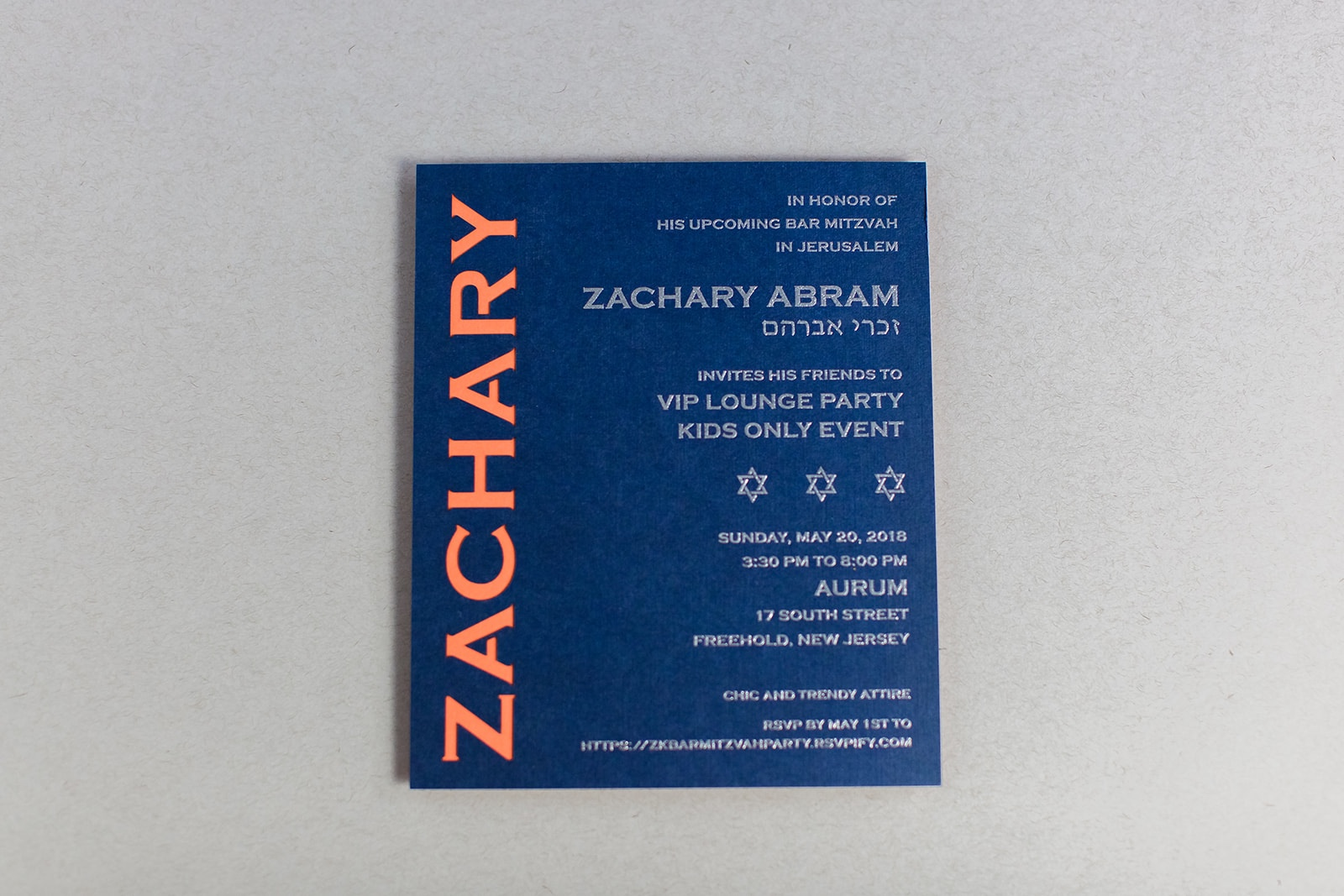 lasercut name reveals fun orange accent layer beneath this blue bar mitzvah invitation printed in silver.  Lasercut nickname reveals a yellow accent layer beneath this navy blue square bar mitzvah invitation.  Staccato proudly serves mitzvah celebration in northern Virginia, DC, and Maryland, and ships nationwide.