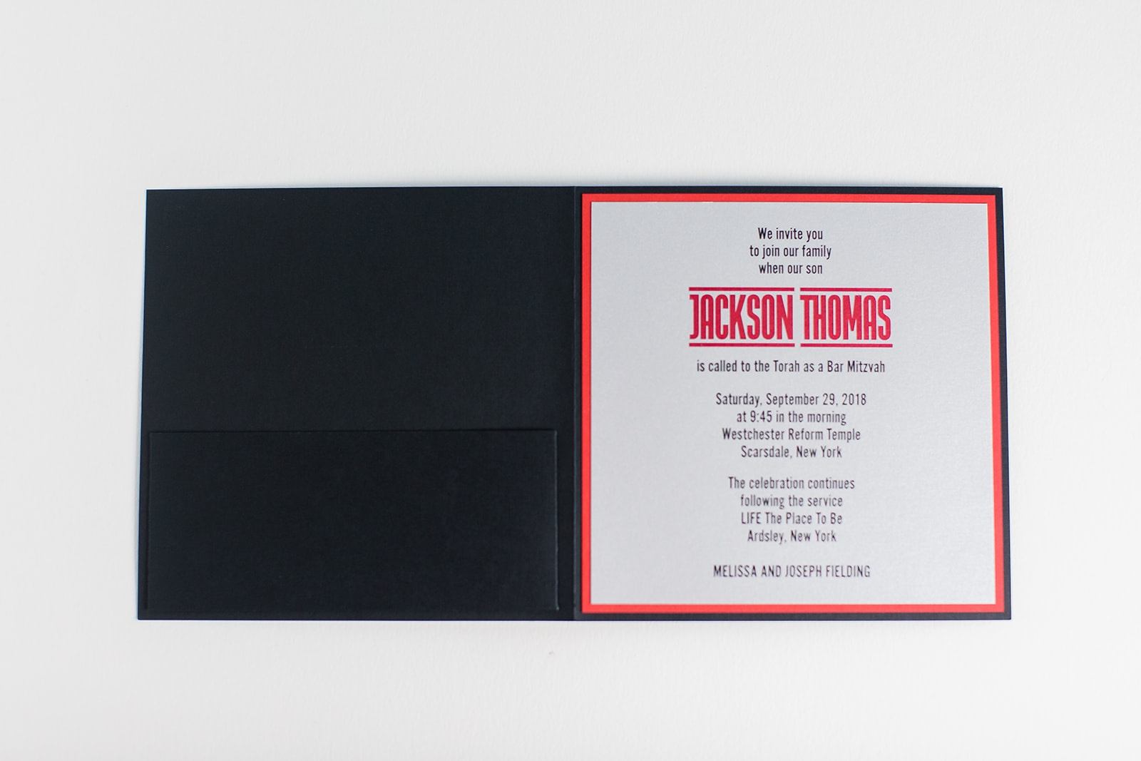 A fun pocketfolio features red and black printing.  Modern Bar Mitzvah invitations in Fairfax, Virginia.