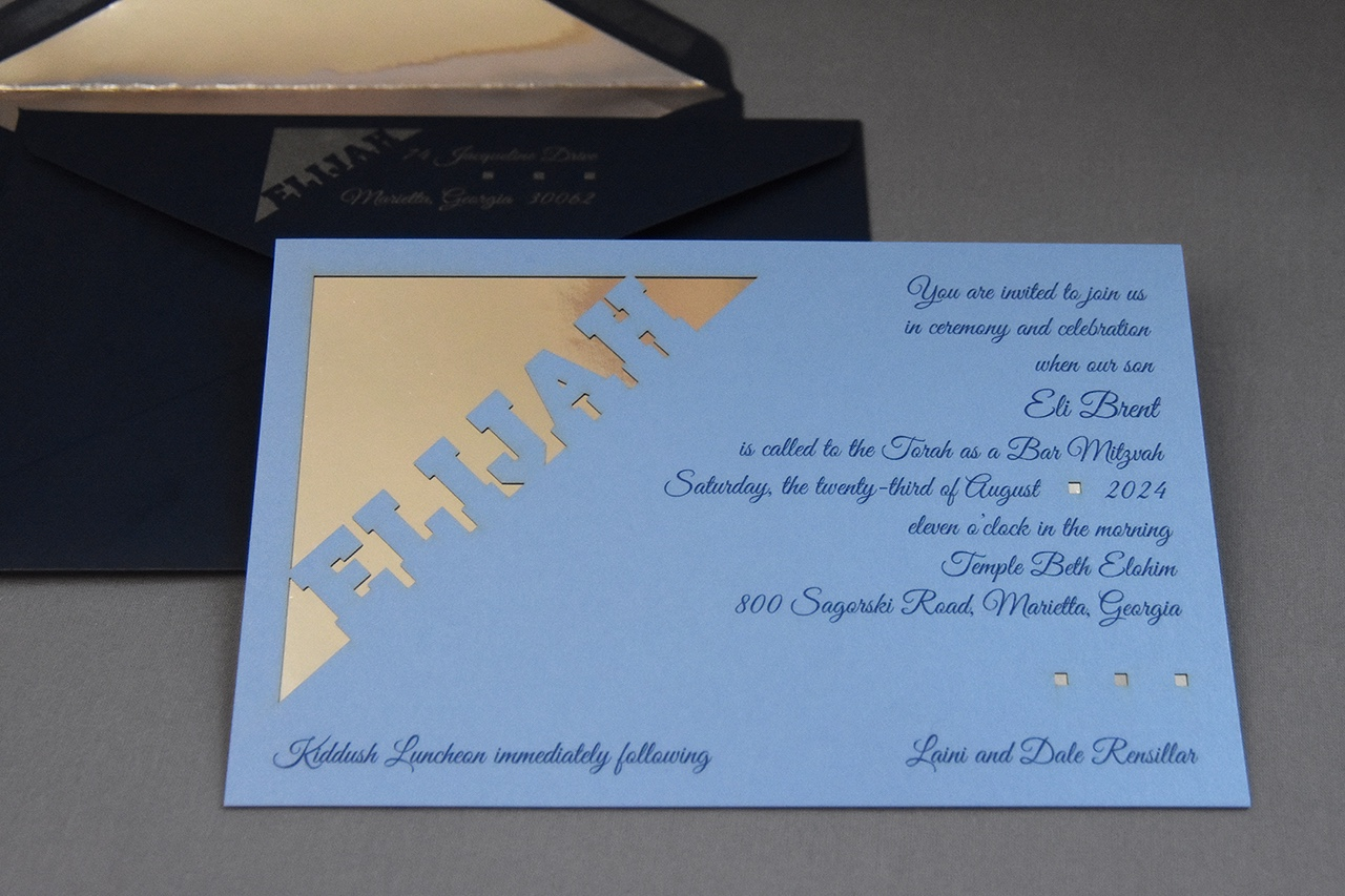 Elijah Brent bar mitzvah invitation features a blue card with lasercut design layered onto a silver mirror.