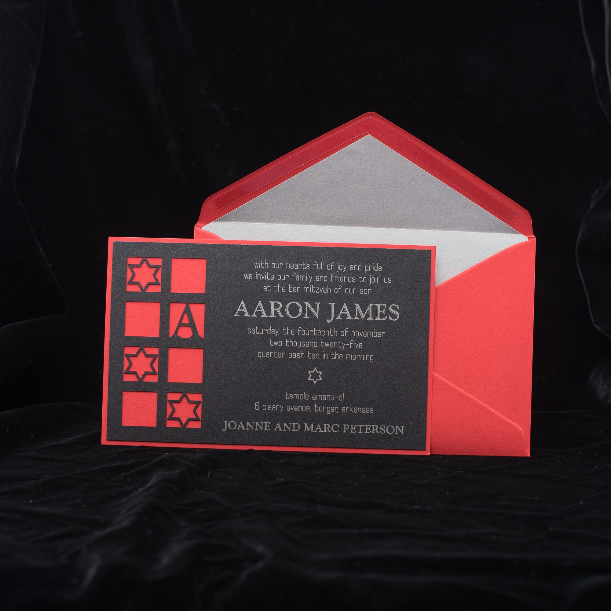 Star of david and initial are featured in lasercut windows of this contemporary bar mitzvah invitation in black, silver, and red.  Staccato proudly serves mitzvah celebration in northern Virginia, DC, and Maryland, and ships nationwide.