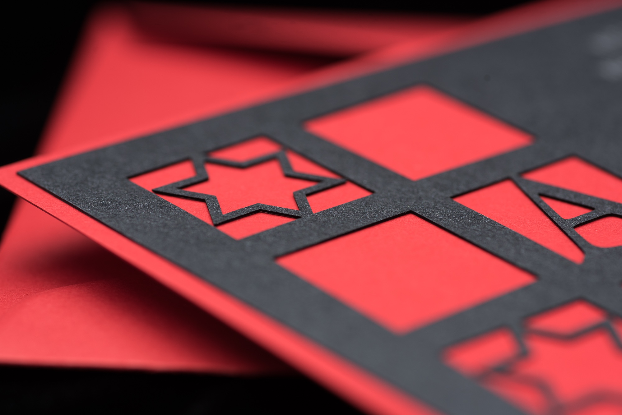 diecut bar mitzvah invitation features windows of monogram and star of david, silver thermography on black paper layered to reveal red below.