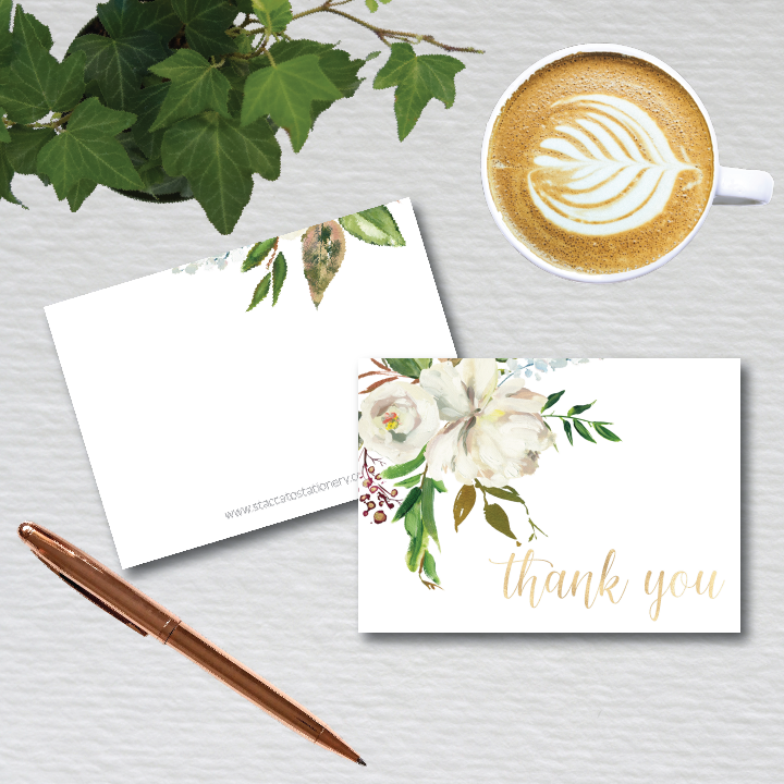 """beautiful white and greenery floral motif is accent with gold foil """"thank you"""" in a beautiful calligraphy script. folded note cards come with blank envelopes"""