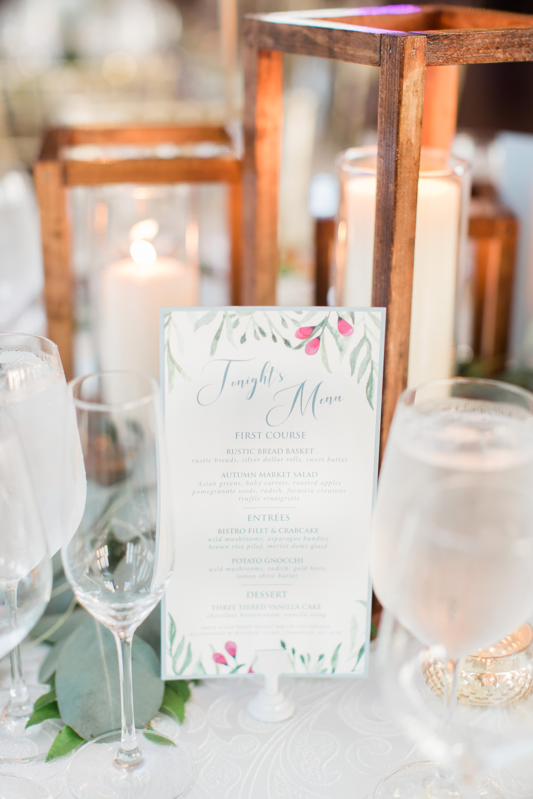 Custom dinner menus with greenery and a soft dusty blue backing layer.