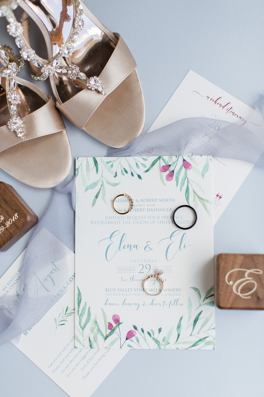 Custom wedding invitations feature greenery a pop of cranberry and a soft dusty blue color.