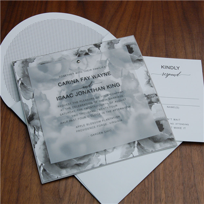 Tuileries wedding invitation by Checkerboard features a pretty floral motif behind a vellum invitation held in place with a pretty silver brad.