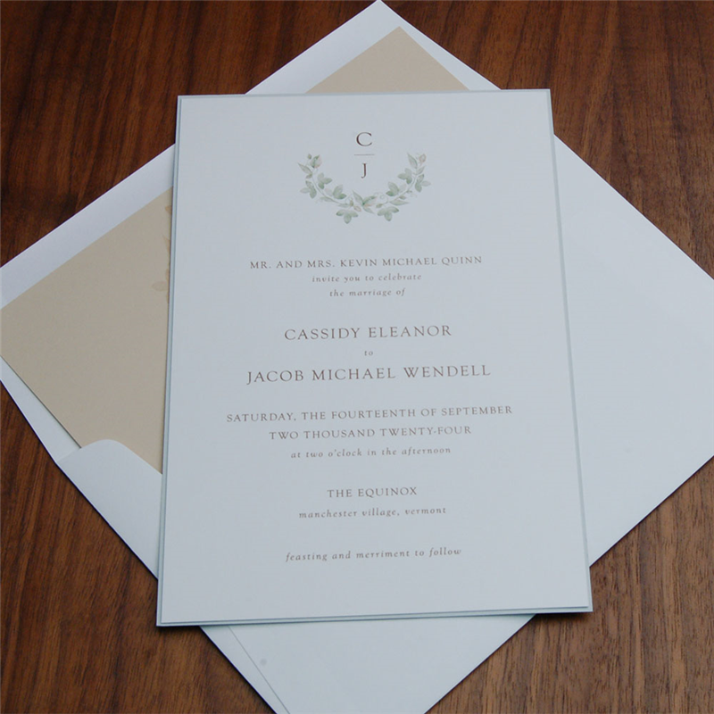 Layered wedding invitation by Checkerboard features ivy greenery around a modern monogram.