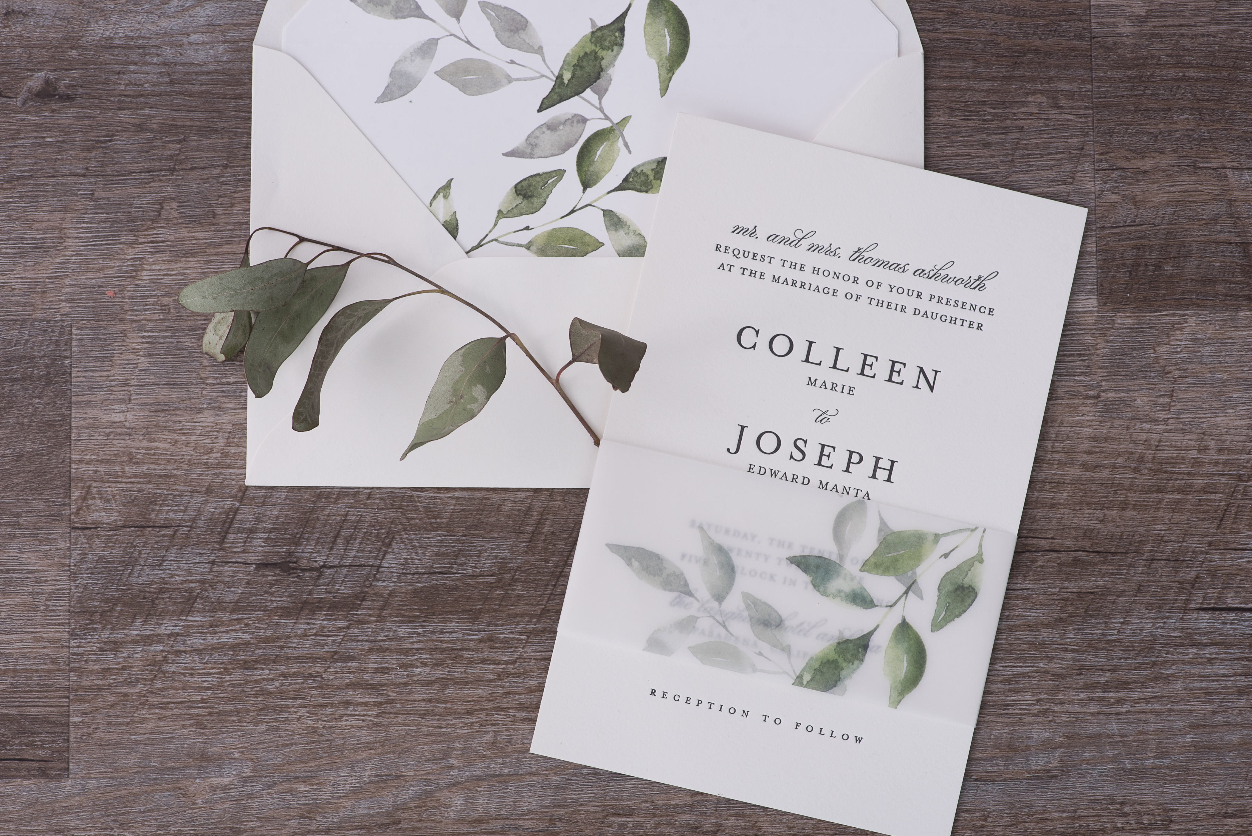Greenery leaves on a vellum wrap and beautiful envelope liner embellish this stunning letterpress wedding invitation.